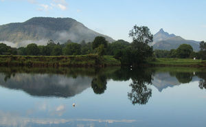Hills and shoreline reflected in river