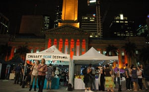 Market stalls on King George Square with City Hall lit up in the evening in the brisStyle indie twilight markets.